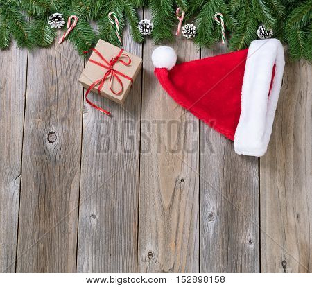 Christmas holiday wooden background with fir branches Santa cap and gift box forming upper border
