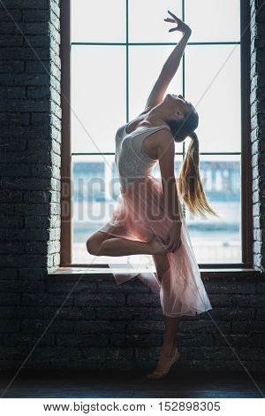 Free form dancing. Attractive young dancer staying in dance pose with window on background