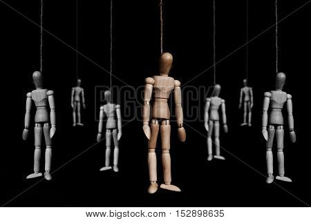 Group of wooden marionettes puppet hangman by rope, on black background