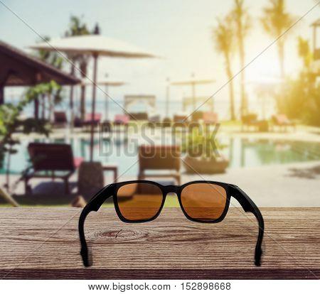 Sun glasses on wooden desk at tropical beach resort in sunset