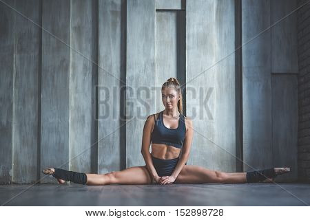 Be yourself. Beautiful slim fitness woman stretching exercise, sitting on splits near wall in studio