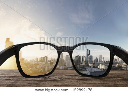 Sun glasses on wooden desk with tropical city view in sunrise view background