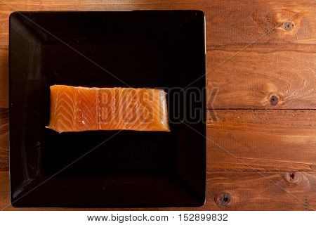 Fresh red fish in a black plate on a wooden background