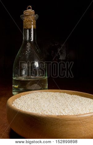 Sesame seeds and sesame oil on a dark background