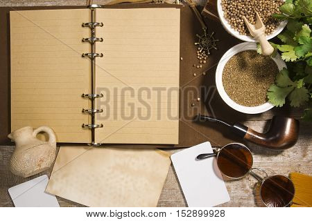 Diary for records and coriander on old wooden table