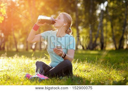 Woman Runner Sitting On The Grass And Drink Fresh Green Detox Smoothie.