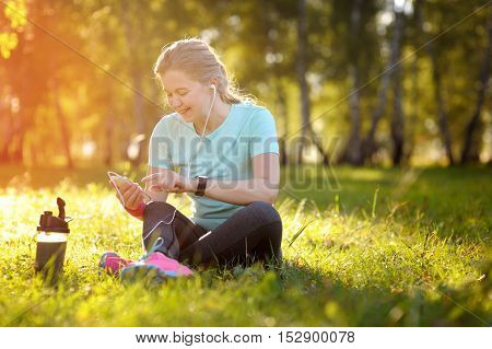 Woman Runner Sitting On The Grass Using A Smart Phone.