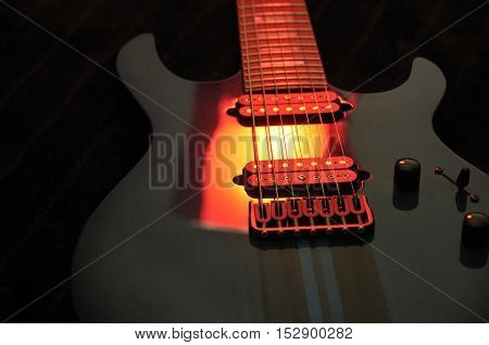 Closeup of electric guitar with bright red light