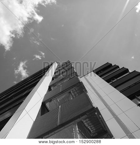 Low angle monochrome view of business building against sky and clouds
