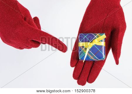 Hands Of Woman In Gloves Showing Gift For Christmas Or Other Celebration