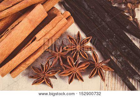 Vintage Photo, Cinnamon Sticks, Vanilla, Star Anise And Cloves On Wooden Surface
