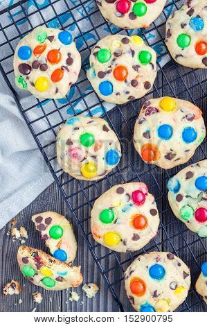 Shortbread cookies with multi-colored candy and chocolate chips on cooling rack vertical top view