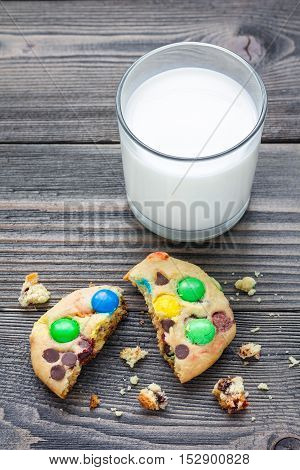 Shortbread cookies with multi-colored candy and chocolate chips served with glass of milk vertical