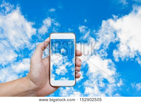 Man hand holding and screen shot blue sky background with white clouds