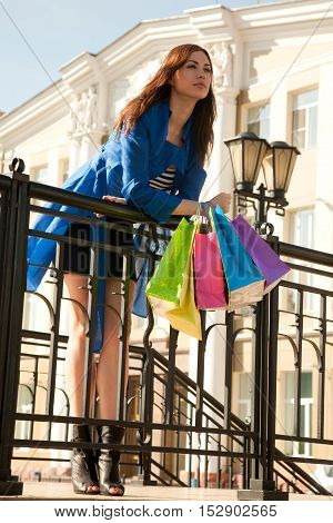 Cheerful young woman takes a walk after good shopping