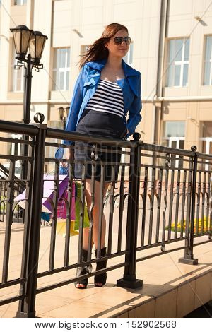 Cheerful young woman is walking in the city after good shopping