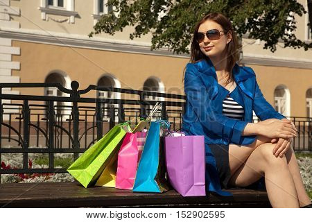 Cheerful young woman is sitting on the bench with shopping bags