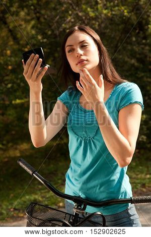 Cheerful young woman in the park with bicyclelooking at mirror