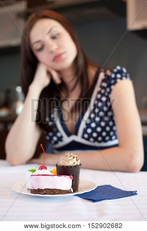 Young woman is dreaming about cake.Focus on the foreground