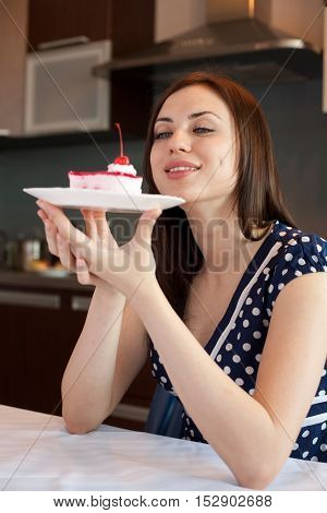Young woman admires her cake at her kitchen