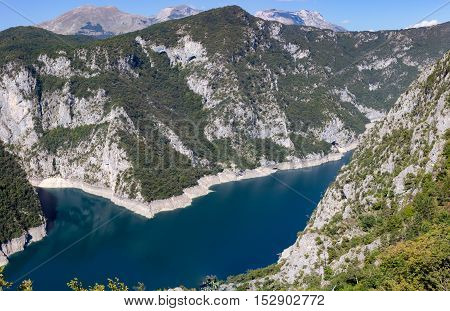 Piva lake pink surrounded by high mountains.