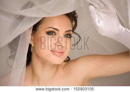 Young charming bride is holding the veil