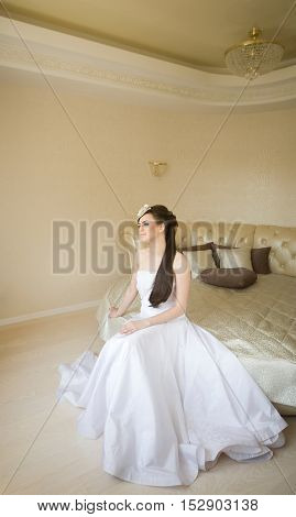 Charming bride is sitting on the bed