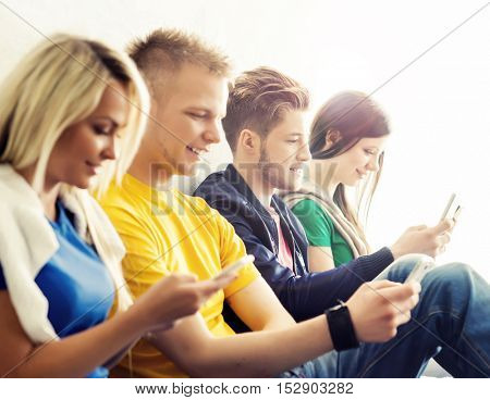 Happy students with a smartphones. Social network and internet concept.