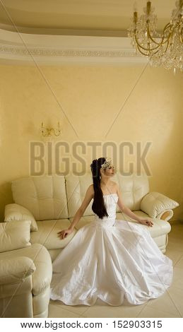 Charming bride is sitting on the couch