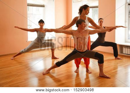 Yoga group practicing under instructors guidance indoors
