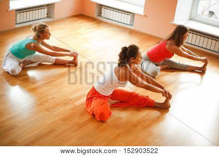 Women practicing yoga at health club indoors