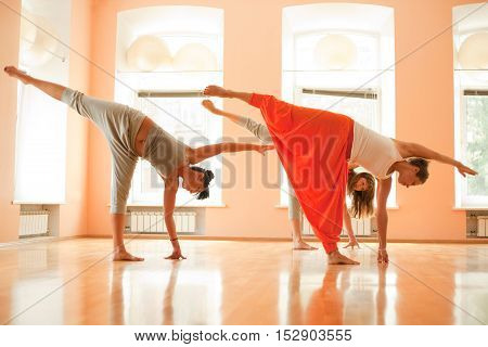Real yoga instructor at classroom showing exercise