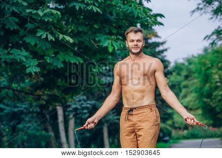 fitness, sport, training and lifestyle concept - healthy athlete bare-chested jumping with skipping rope outdoor.