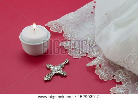 White vintage lace christening dress candle and cross pendant isolated on red background