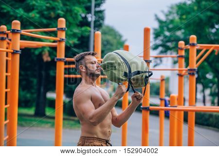 a young man leads a healthy lifestyle, engaged in outdoor sports using SANDBAG