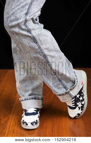 Woman jeans and sneaker shoes on wooden floor