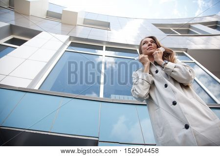 Woman is standing near modern building.Low Angle View