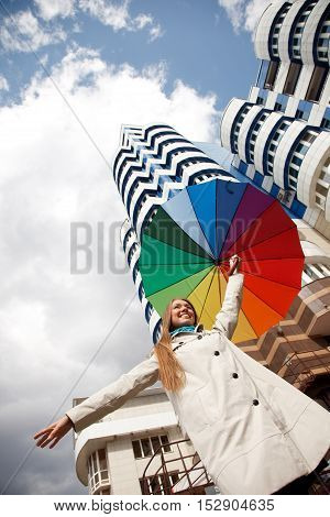 Cheerful woman is standing near modern building with colorful umbrella .Low Angle View