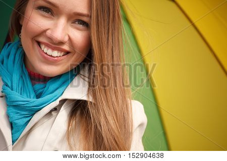 Young woman standing on the street with color umbrella