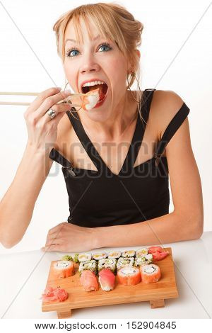 Young woman is opening her mouth and eating sushi