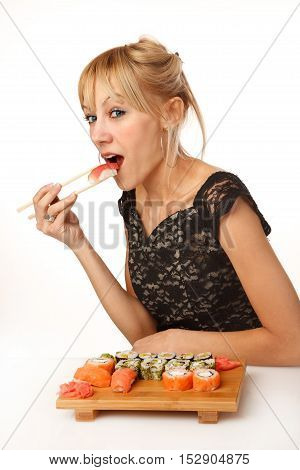 Young woman is opening her mouth and eating sushi with chopsticks
