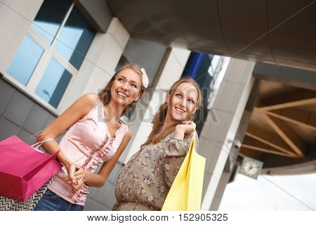 Two cheerful young women with shopping bags outdoors.Low angle view