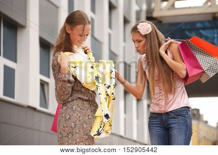 Two girls with shopping bags standing on the street one of the girls envy of new dress another girl