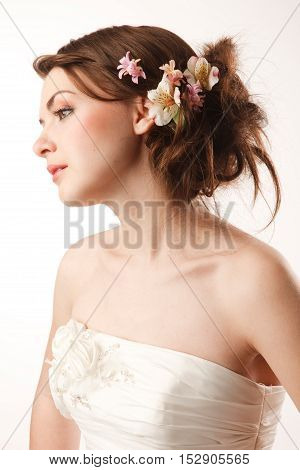 Beatiful brides profile with real flowers in her hair