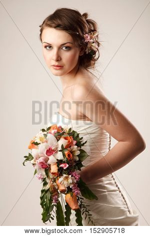 Charming sensual bride looking at camera and holding her bouquet