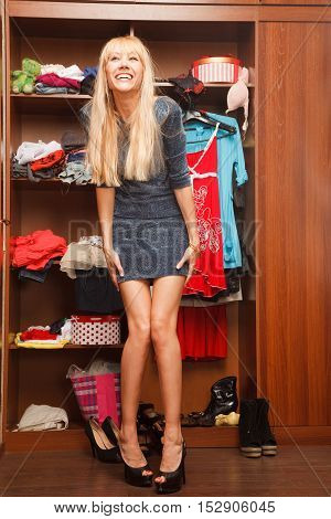 Beautiful young woman stands near her wardrobe