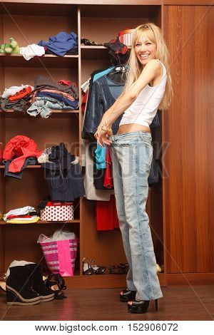 Young stylish woman stands near her wardrobe and surprised that her jeans are now to big for her