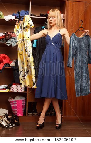 Beautiful young woman stands near her wardrobe with two different dresses and trying to choose