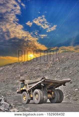 Heavy dump truck on the iron ore opencast on a sunset