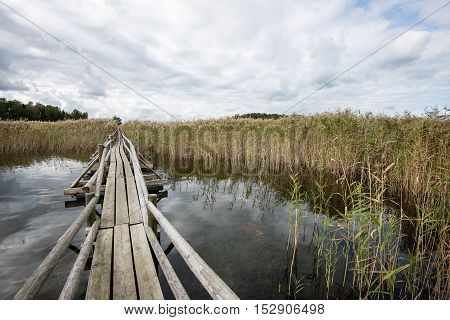 Diminishing Perspective Of Wooden Suspension Footbridge Over River